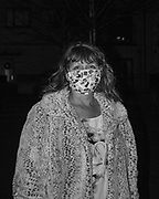 Lorraine Cash wears a mask she made as she walks around Orchard Village to see other resident's Christmas decorations after the sun has gone down.