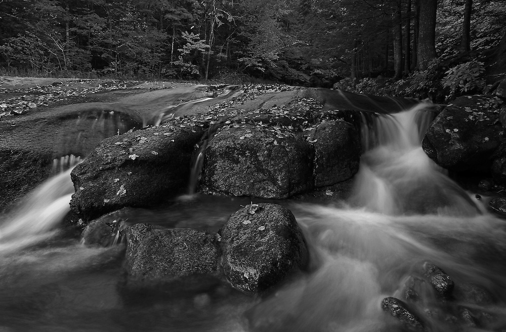 This intimate black and white landscape photography image of Flume Brook at Franconia Notch State Park near Lincoln in the New Hampshire White Mountains region features silky water tumbling down the creek during New England fall foliage season. Table Rock is a small section of Conway granite in this New Hampshire State Park that was exposed and outcropped of hundreds of years. This scenic New Hampshire cascading water section is 500 feet long and 75 feet wide.<br /> <br /> This NH B&W landscape photography image is available as museum quality photography prints, canvas prints, acrylic prints or metal prints. Black and white photography fine art prints may be framed and matted to the individual liking and decorating needs:<br /> <br /> http://juergen-roth.pixels.com/featured/new-hampshire-table-rock-nature-juergen-roth.html<br /> <br /> All photographs are available for digital and print image licensing at www.RothGalleries.com. Please contact me direct with any questions or request.<br /> <br /> Good light and happy photo making!<br /> <br /> My best,<br /> <br /> Juergen<br /> Prints: http://www.rothgalleries.com<br /> Photo Blog: http://whereintheworldisjuergen.blogspot.com<br /> Twitter: @NatureFineArt<br /> Instagram: https://www.instagram.com/rothgalleries<br /> Facebook: https://www.facebook.com/naturefineart