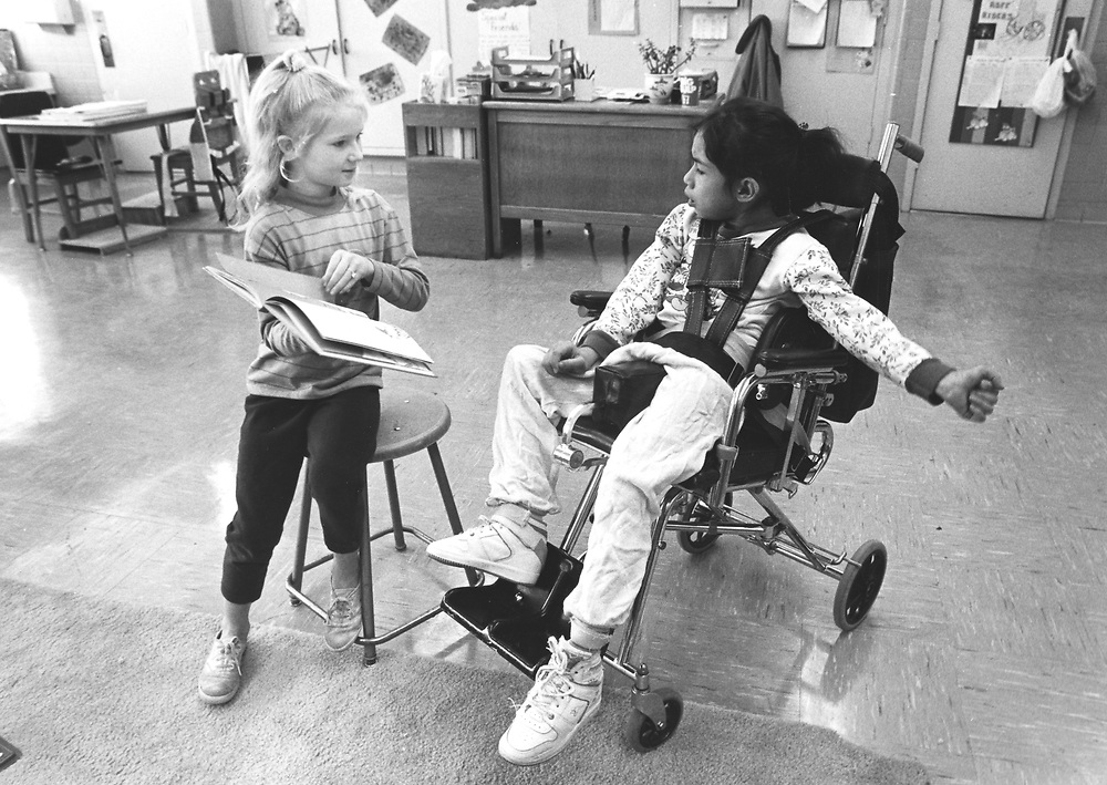 ©1989 4th grade girl reading to Cerebral palsy student in public school classroom.   NO releases.