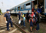Migrants are moved from the train they were travelling in to coaches by Hungarian police, close to Gyor, Hungary, September 3 2015. An estimated 3,000 people were believed to be camped out at the station as authorities opened the doors to those without European visas or travel documents to board trains.