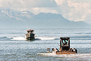 Fishing boats drive up to an awaiting tractor tug that will carry them back to land on the beach at Anchor Point, Alaska. The unique boat launch uses logging skidders to tow fishing boats from the Cook Inlet up the steep beach to the parking area and is the result of extreme tide that would make launching a boat impossible otherwise.