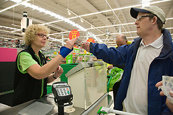 Day Service user with learning disability paying for his shopping at the Supermarket check out,