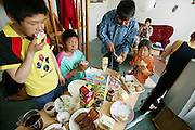 (MODEL RELEASED IMAGE). Breakfast at the Madsen family's home has a little bit of everything. From sandwiches to cereal, everyone helps themselves to their morning meal. Emil (in blue shirt) stands in between his daughter Belissa and nephew Julian, 10. Abraham stands to the left of Julian, and Erika sits on the couch behind. This is an especially big and varied breakfast because Emil had been on hunting trip for a week and had just returned the night before, after collecting money in Ittoqqortoormiit, buying supplies in the store there and returning to his village on his dogsled (1.5 hours). (Supporting image from the project Hungry Planet: What the World Eats.)