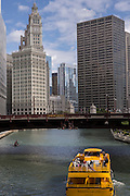A water taxi travels the Chicago River by Wabash Ave in Chicago, IL.