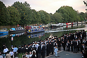 Men praying and casting away their sins into the river Lea, Hackney, London for Tashlich. Tashlich is a Jewish practice that is performed during Rosh Hashanah (Jewish New Year). Men and women gather near a large body of flowing water and symbolically 'cast off' the previous year's sins by throwing pieces of bread into the water while reading a prayer (the last verses from the prophet Micah).