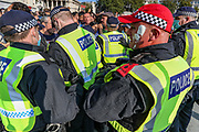 """What it appears as an ice-cream is thrown at a police officer's left cheek during a """"Resist and Act for Freedom"""" protest against a mandatory coronavirus vaccine, wearing masks, social distancing and a second lockdown, nearby Canada House in Trafalgar Square, London on Saturday, Sept. 19, 2020. The event, which began at noon, drew a broad coalition including coronavirus sceptics, 5G conspiracy theorists and so-called """"anti-vaxxers"""". Speakers at the event accused the government of attempting to curtail civil liberties. (VXP Photo/ Vudi Xhymshiti)"""