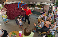 Larry Frates along with his assistant Lulu Sachetta perform a little magic for the crowd during the Laconia Outdoor Market Thursday afternoon.  (Karen Bobotas/for the Laconia Daily Sun)