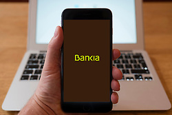Using iPhone smart phone to display website logo of Bankia Spanish bank.