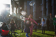 An entertainer makes giant soap bubbles in the spring sun outside the National Gallery in Trafalgar Square. A small group of children of all ages play and laugh and try to grab the bubbles as the float by in the air. It is sprin time and the air warm.