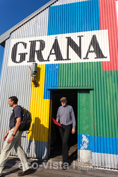 People walking out of the colourful Grana, a recreated Herring Factory that is part of the Herring Era Museum, depicting life in this herring village during the 1940s and 1950s. Siglufjordur, Iceland. July.