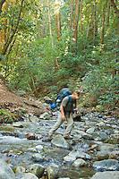 Backpacker crosses a stream on Pine Ridge Trail, Big Sur, California.