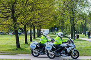 Two police motorbikes make a sweep of the common to check enforcement of the guidance - Clapham Common is pretty quiet now Lambeth Council has taped up all the benches, put up signs and organised patrols by wardens. The 'lockdown' continues for the Coronavirus (Covid 19) outbreak in London.