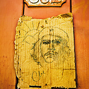 A portrait of Ernesto Che Guevara sketched on a piece of cardboard hanging on a door in the town of Trinidad, Cuba.<br />