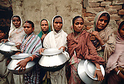 The poor queuing for food outside Mother Teresa's Mission in Calcutta, India.  The women are carrying metal pots in which to carry the food back to their families.