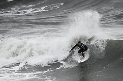 © Licensed to London News Pictures. 25/08/2020. City, UK. A surfer enjoying the waves at Langland Bay, Gower, as Storm Francis brings poor weather conditions across the UK with high winds and heavy rain causing disruption. Photo credit: Robert Melen/LNP