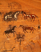 Nineteenth century Navajo pictographs of horses and riders with other animals done in charcoal and paint, shallow cave in Canyon del Muerto, Canyon de Chelly National Monument, Arizona.