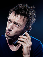 studio portrait on black background of a funny expressive caucasian man phoning anguish