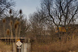 Union Pacific Locomotive 8776, a EMD SD70ACe model engine pulls a long line of freight cars southward over the bridge at Stringtown Road in rural Shirley Illinois.