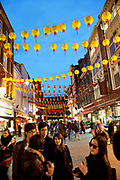 Chinese New Year on Gerrard Street, Soho. Also known as Chinatown. Local Chinese community gather on this famous area of central London which is the focus of celebrations for this, the Chinese Year of the Rabbit. Bright red and yellow lanterns are strung across between the buildings creating a canopy of colour.