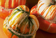 Close up selective focus photograph of a few Turban Squash on a butcher block table
