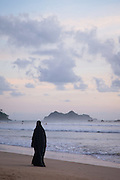 Woman wearing Niqab walking beside the sea, Red Island Beach, Red Island, Banyuwangi Regency, East Java, Indonesia, Southeast Asia