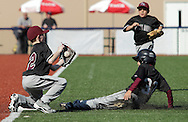 Chester, New York - A baserunner slides into third base as the third baseman catches the throw during the TRUMP March Madness youth baseball tournament at The Rock Sports Park on March 17, 2012.