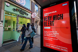 © Licensed to London News Pictures. 17/12/2020. LONDON, UK. Women wearing facemasks pass a bus stop on Shaftesbury Avenue in Soho which displays a digital sign showing the current Tier 3, Very High Alert Level, restrictions as the coronavirus pandemic continues.  Photo credit: Stephen Chung/LNP