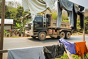 15 MARCH 2013 - ALONG HIGHWAY 13, LAOS:  A dump truck goes past clothes drying along the side of Highway 13 north of Luang Prabang, Laos. The paving of Highway 13 from Vientiane to near the Chinese border has changed the way of life in rural Laos. Villagers near Luang Prabang used to have to take unreliable boats that took three hours round trip to get from the homes to the tourist center of Luang Prabang, now they take a 40 minute round trip bus ride. North of Luang Prabang, paving the highway has been an opportunity for China to use Laos as a transshipping point. Chinese merchandise now goes through Laos to Thailand where it's put on Thai trains and taken to the deep water port east of Bangkok. The Chinese have also expanded their economic empire into Laos. Chinese hotels and businesses are common in northern Laos and in some cities, like Oudomxay, are now up to 40% percent. As the roads are paved, more people move away from their traditional homes in the mountains of Laos and crowd the side of the road living off tourists' and truck drivers.   PHOTO BY JACK KURTZ