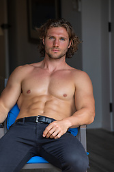 shirtless muscular man sitting in a chair at home