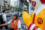 "Mar. 20, 2009 -- BANGKOK, THAILAND:  A motorcycle taxi passes a Ronald McDonald performing a traditional Thai ""Wai"" (greeting) in front of McDonald's fast food restaurant on Sukhumvit Rd. in Bangkok.  Photo by Jack Kurtz"