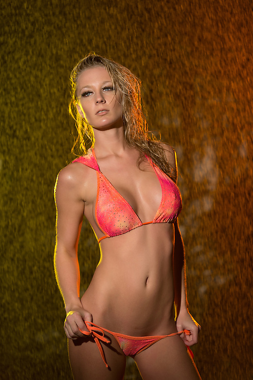 Wet caucasian woman wearing pink bikini in her seductive pose in a colorful backdrop