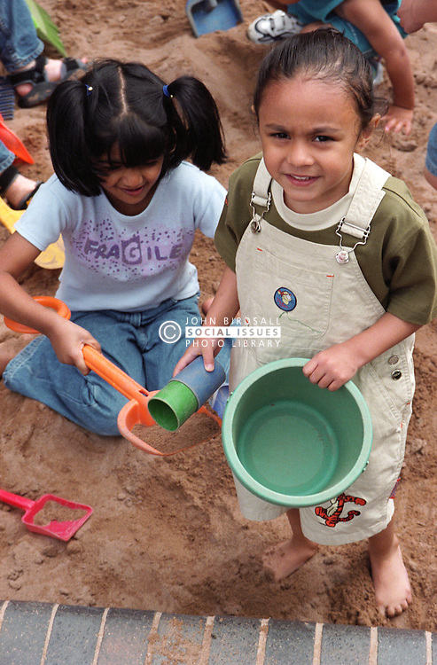 Nursery school girls using bucket and spade to play with sand in playground sandpit,