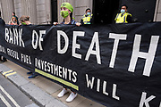 Bank of Death banner outside the Bank of England at the Walk of Shame disruptive mach through the City of London by environmental group Extinction Rebellion on 4th September 2020 in London, United Kingdom. The walk visited various locations in the financial district, to protest against companies and institutions with historical links to the slave trade, or who finance or insure projects which are seen as ecologically unsound. The message by the group is that 'apologies and token attempts at diversity are not enough to address this legacy and present reality. Our demand is reparations and reparatory justice for those affected by colonial and neo-colonial exploitation'. Extinction Rebellion is a climate change group started in 2018 and has gained a huge following of people committed to peaceful protests. These protests are highlighting that the government is not doing enough to avoid catastrophic climate change and to demand the government take radical action to save the planet.