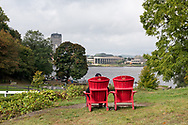 Adirondack chairs with a view of the Ottawa River and the Canadian Museum of History (Museum of Civilization) in Gatineau Québec.<br /> Photographed next to Ottawa Locks 1-8 on the Rideau Canal in Ottawa, Ontario, Canada.
