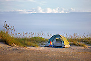 A tent is set up for summer camping in the dunes of the North Carolina coast