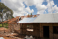 nyrasunge Rwanda.Photo Randy Vanderveen.Nyrusange, Rwanda.Rwandan workers install a tin roof on a new classroom.