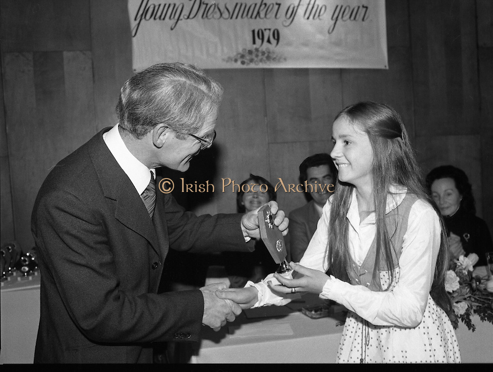 Young Dress Designer of the Year.     (M75).1979..22.05.1979..05.22.1979..22nd May 1979..The Cassidy Fabrics sponsored Young Dress Designer of the Year, make and model competition was held today in Liberty Hall,Dublin. The overall winner of the competition was Ms Marianne Byrne (15),Cabinteely,Co Dublin. Ms Byrne is a pupil at the Cabinteely Community School...Image shows Mr Michael Cassidy,Director Cassidy Fabrics, presenting an award to a section winner..Unfortunately we do not have her name, if you know her why not let us know at irishphotoarchive.ie
