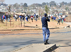 South Africa - Johannesburg - 24 August 2020 - A police officer fires rubber bullets at protestingElias Motsoaledi informal settlement community members who barricadedroads with burning tyres and debris in Soweto. Picture: Itumeleng English/African News Agency(ANA)