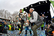 Seattle Sounders forward Will Bruin, left, midfielder Cristian Roldan, right, with honorary teammate, Bheem Goyal, center,  lift the 2016 and 2019 MLS Cup trophies during the MLS Cup Champions Parade & Rally on November 12, 2019 in Seattle, Washington, to celebrate the Sounders' win over Toronto FC to win the MLS Cup soccer match in Seattle. (Alika Jenner/Image of Sport)