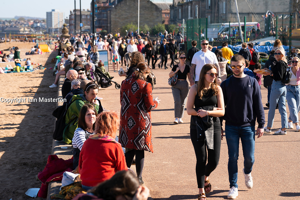 Portobello, Scotland, UK. 3 April 2021. Easter weekend crowds descend on Portobello beach and promenade to make the most of newly relaxed  Covid-19 lockdown travel restrictions and warm sunshine with uninterrupted blue skies. Pic; Promenade busy with members of the public enjoying the weather.  Iain Masterton/Alamy Live News