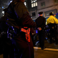 """Lights illuminate a police officer's handgun as he monitors activity during a """"Queer Rage"""" dance party outside the location of the 2017 """"Congress of Tomorrow"""" Joint Republican Issues Conference in Philadelphia, Pennsylvania, U.S. January 25, 2017."""