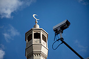 Minaret and a CCTV camera at the East London Mosque on Whitechapel High Street in the East End of London. It is from here that the call to prayer can be heard. This area in the Tower Hamlets is predominantly Muslim with just over 50% from Bangladeshi descent. This is known as a very poor area of London's East End.
