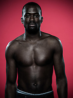 one young handsome african man topless portrait in studio on red background