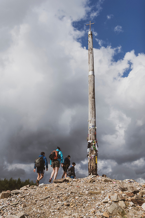 A Spanish family walking the Camino de Santiago arrive at the Cruz de Ferro, or Iron Cross, a landmark and, at 1530 meters, the highest point on the Camino Frances. Many pilgrims deposit a stone brought from home at the base of the cross. (July 1, 2018)