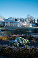 The conservatory surrounded by frost covered plants  in the Italian garden at Chiswick House, Chiswick, London, UK