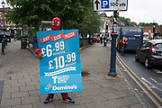Spiderman with a Dominoes Pizza advertising board in Moseley, Birmingham, England, United Kingdom.