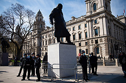 Police officers stand by a statue of Winston Churchill during a 'Kill The Bill' protest against The Police, Crime, Sentencing and Courts Bill in Parliament Square, London. Picture date: Saturday April 17, 2021.
