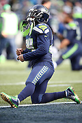 Seattle Seahawks running back Marshawn Lynch (24) sports gold bottom cleats as he stretches in the end zone during pregame warmups before the NFL week 20 NFC Championship football game against the Green Bay Packers on Sunday, Jan. 18, 2015 in Seattle. The Seahawks won the game 28-22 in overtime. ©Paul Anthony Spinelli