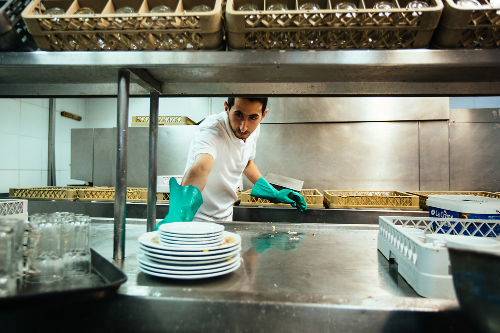 Mohanad Farajallah, 24, a Jordanian employee from Aqaba is seen washing dishes in the kitchen of the Isrotel Lagoona Hotel in Eilat, southern Israel, on March 14, 2018.