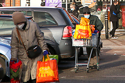 © Licensed to London News Pictures. 14/12/2020. London, UK. A couple wearing face coverings are seen with shopping bags outside Sainsbury's in north London. With coronavirus restrictions  and a possible No-Deal Brexit outcome from the EU-UK trade negotiations, members of public are stocking up supplies of food and other items. Health officials are concerned about a sharp rise in coronavirus infection rates in London which means the capital may go into tier three tougher lockdown restrictions. Photo credit: Dinendra Haria/LNP